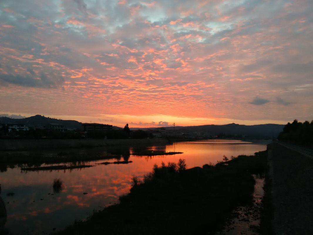 一抹瑰丽的朝霞,像溶化的水彩,令人神怡。朝霞映照的河水变幻着色彩,如霜枫,如榴火,如玛瑙,如琥珀,又像一片片重重叠叠的红色鱼鳞,不一会有变成了金蓝色的鱼鳞,好美的一幅图画。2016年6月25日5点20健走途中,摄于陇县新建路南河大桥。